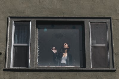 Woman staring out the window during the coronavirus lockdown.