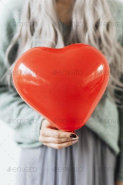 Woman holding a heart balloon