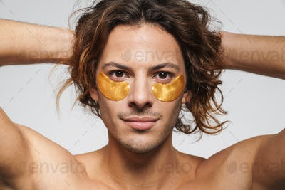 Pleased shirtless guy with eye patches looking at camera