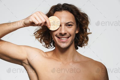 Happy shirtless guy smiling while posing with cosmetic sponge