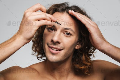 Pleased shirtless guy smiling while plucking eyebrows with tweezers