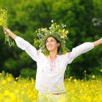 Young smiling woman standing and holding yellow flowers in meadow