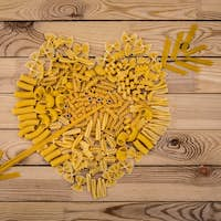 Directely above view of heart made of different kind of pasta. Wooden background