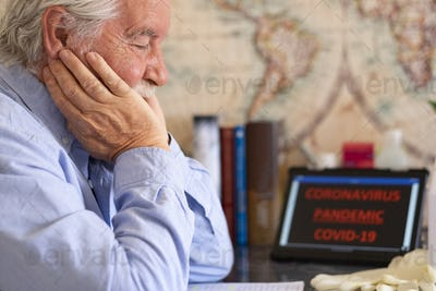 Coronavirus epidemic. Sad and depressed senior man at home worries about the infection from COVID-19