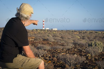 Adult senior man with cap indicates the light house on the cliff, tropical area with volcanic rocks