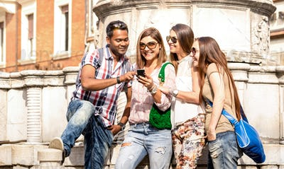 Multiracial friends using mobile smart phone at city tour