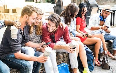 Multiracial millennials group using smart phone at city college backyard