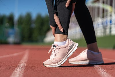 woman runner touching foot in pain due to sprained ankle. Running sport, injury from workout