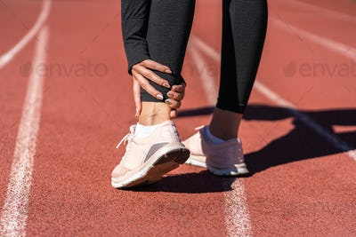 Athletic woman runner touching foot in pain due to sprained ankle. Running sport injury from workout