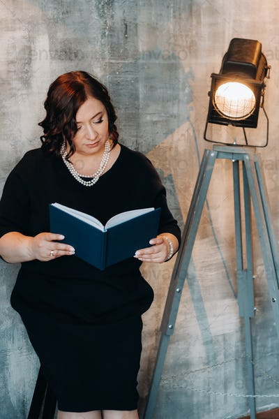 A businesswoman in a black beaded dress stands against the wall with a book in her hands