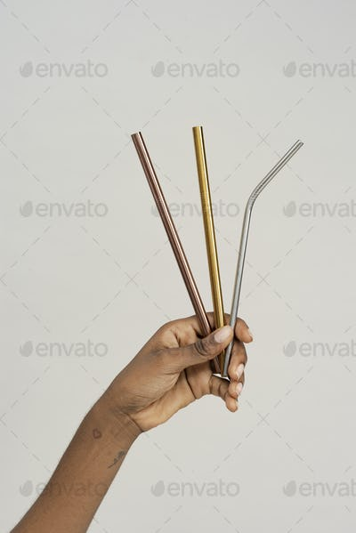Hand holding reusable metal straws