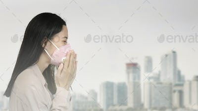 Asian woman wearing a mask and coughing in a polluted city
