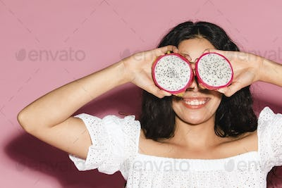 Woman covering her eyes with sliced dragon fruits