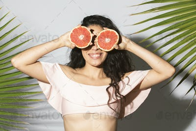 Cheerful woman covering her eyes with sliced grapefruit