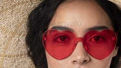 Woman wearing a hat and a red vintage heart-shaped sunglasses