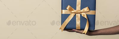 Woman holding a present against a beige background