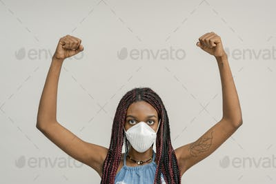 Black woman wearing a mask and raising her hands up in the air