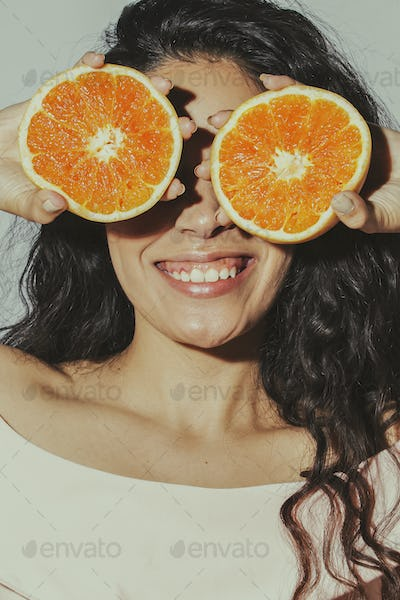 Cheerful woman with sliced oranges covering her eyes