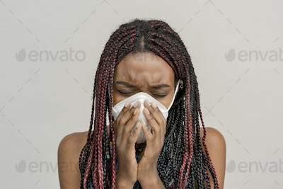 Black woman wearing a mask and coughing