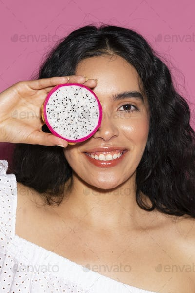 Woman covering her eyes with a sliced dragon fruit