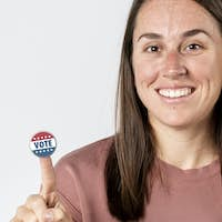 Cheerful woman with a vote sticker on her index finger