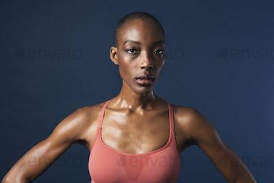 Black woman in sportswear on navy blue background