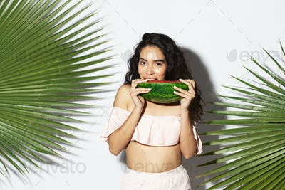 Happy woman biting into a slice of watermelon