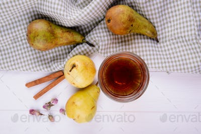 top view of fresh ripe pears and a glass of juice with cinnamon sticks on plaid tablecloth