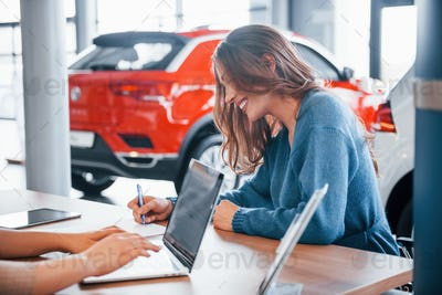 Cheerful woman sits with assistant in car shop and buying new vehicle
