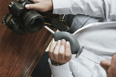 Man cleaning his camera lens with a rubber air blower