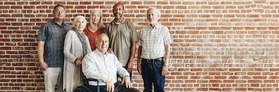 Happy elderly man on a wheelchair with friends