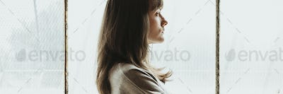 Brown hair woman standing by a window