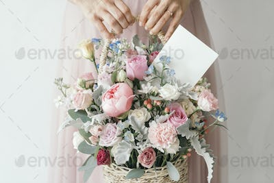 Hand carrying a basket filled with assorted colorful flowers and a note card