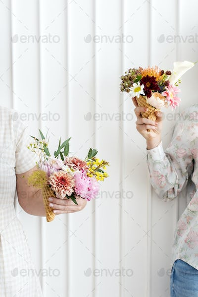 Two women holding up flowers in ice cream cones