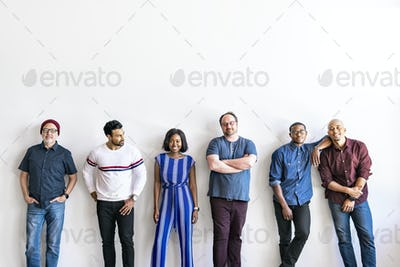 Group of people standing in a by a white wall