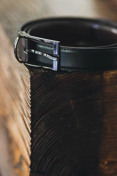 Black men's belt on a wooden stand