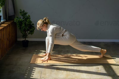 A woman in white sportswear in the gym on the mat is exercising. Sports training, healthy lifestyle.