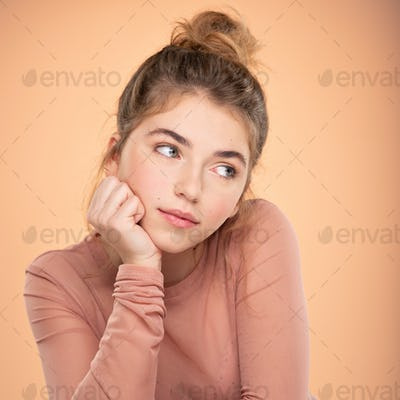 Closeup portrait of an young  girl over colored background.  Fashion model posing at studio.