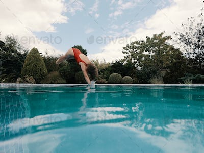 Slender girl dives into the pool
