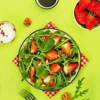 Summer Strawberry Salad with spinach leaves, arugula, walnuts and balsamic vinegar and olive oil
