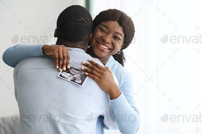Emotional black woman holding ultrasound image and hugging her husband