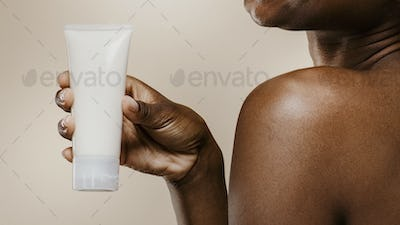 African woman holding cosmetics