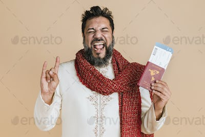 Happy Indian man in a kurta holding a passport with flight tickets