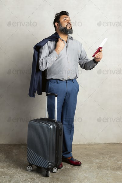 Happy Indian businessman checking the departure board at the airport