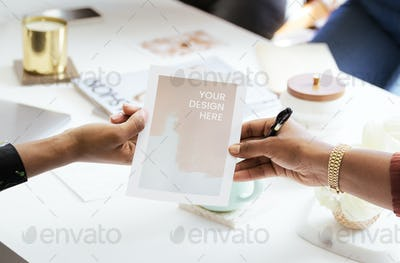 Woman handing a paper mockup in the meeting room