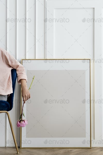 Woman holding a flower sitting by a frame mockup