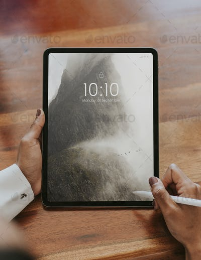 Business person using a wireless stylus with a digital tablet mockup in a meeting