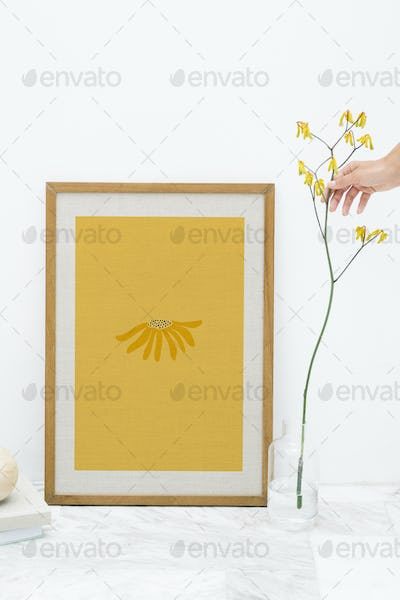 Photo frame mockup by a yellow forsythia