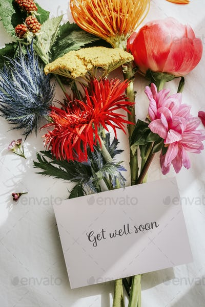 Bouquet of colorful flowers on a white bed sheet with a card mockup