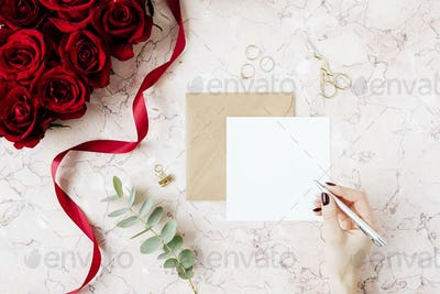 Woman writing on a card mockup by a bouquet of red roses